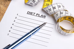 Close up of paper with blank diet plan, pen and measure tape Stock Photo