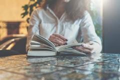Close-up of paper book, notebook, diary on table in cafe. Businesswoman in white shirt sitting at table and reading book Stock Photography