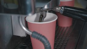 Close-up of paper cup in coffee machine, which is filled by hot black coffee. Coffee brewing. stock footage