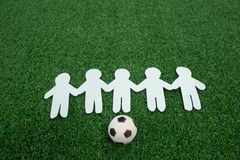 Paper cut outs and footballs arranged on artificial grass. Close-up of paper cut outs and footballs arranged on artificial grass stock photos
