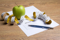 Close up of paper with diet plan, apple and measure tape on tabl Royalty Free Stock Images