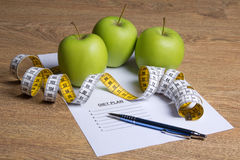 Close up of paper with diet plan, green apples and measure tape Royalty Free Stock Image