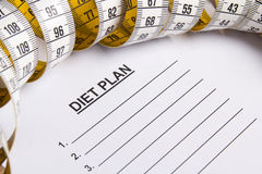 Close up of paper with diet plan and measure tape Royalty Free Stock Photos