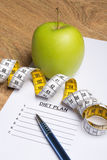 Close up of paper with diet plan, pen, apple and yellow measure Stock Images