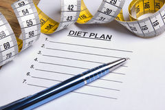 Close up of paper with diet plan, pen and measure tape Royalty Free Stock Images