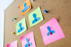 Close up of paper human shapes on cork board Stock Photography