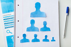 Close up of paper human shapes on notebook Royalty Free Stock Photography