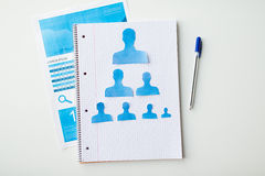 Close up of paper human shapes on notebook Stock Image