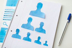 Close up of paper human shapes on notebook Stock Photo