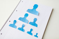Close up of paper human shapes on notebook Royalty Free Stock Image