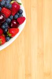 Close up of par of plate full of berries on table Stock Photos