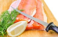 Close up para a faixa de peixes da truta com faca em uma placa da cozinha Fotos de Stock Royalty Free