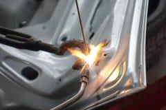 Close up para soldar o auto corpo com tocha do gás fotografia de stock