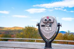 Close up of park binoculars with wooded mountains at the peak of fall foliage in background