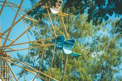 Close up part of colorful ferris wheel with green tree and blue sky background. Royalty Free Stock Image