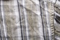 Close up part of a shirt from hemp fabric. Casual man`s shirt with pattern. Wrinkled texture from hemp and cotton background.  royalty free stock photography