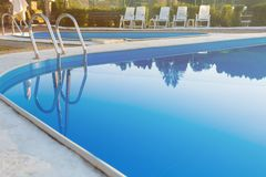 Close-up of a part of swimming pool with a stainless steel ladder and blue water on sunset. Summer vacation, holidays, relax stock image