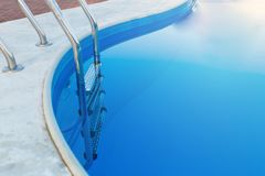 Close-up of a part of swimming pool with a stainless steel ladder and blue water on sunset. Summer vacation, holidays, royalty free stock image