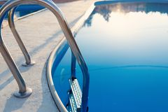 Close-up of a part of swimming pool with a stainless steel ladder and blue water on sunset. Summer vacation, holidays, relax stock images