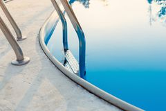 Close-up of a part of swimming pool with a stainless steel ladder and blue water on sunset. Summer vacation, holidays, relax, royalty free stock image