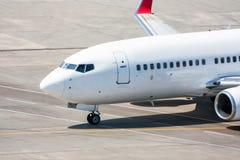 Close-up a parte dianteira do avião comercial que taxiing no avental do aeroporto Imagens de Stock