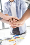 Close-up partial view of businessmen stacking hands while working on project together Royalty Free Stock Image