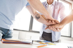 Close-up partial view of businessmen stacking hands while working on project together Stock Image