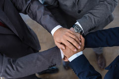 Close-up partial view of businesspeople in formal wear stacking hands together royalty free stock photography