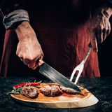Chef in apron with meat fork and knife slicing gourmet grilled steaks with rosemary and chili pepper on wooden board. Close-up partial view chef in apron with Royalty Free Stock Image