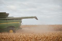 Close up partial view of a combine harvester. Showing the chaff discharging from the rear and mechanical arm as it harvests maize Stock Photos