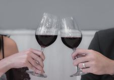 Close-up partial view of lover clinking transparent glasses of red wine. stock image
