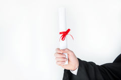 Close-up partial view of student holding diploma. On white Stock Photo
