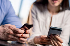 Close-up partial view of young couple using smartphones together. Lunch meeting concept Royalty Free Stock Images