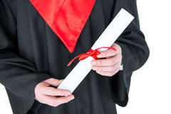 Close-up partial view of young man in graduation gown holding diploma Royalty Free Stock Photography