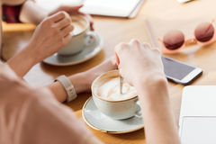 Close-up partial view of young women sitting at table and drinking coffee. Coffee break concept Stock Images