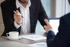 Close up of partners discuss statistics analyzing sales. Close up of male managers discuss company statistics during business meeting, businessmen negotiate on stock images