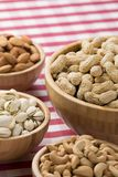 Bowls of peanuts, almonds, pistachios, cashews on red checkered Royalty Free Stock Photo