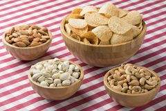 Bowls of potato chips, almonds, pistachios, cashews on red check Stock Image