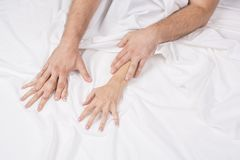 Close up of passionate couple hold hands during making intense love in bedroom, lovers enjoy hot sex on white sheet. Boyfriend and girlfriend relax having royalty free stock photography