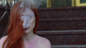 Close up of passionate lady smoking e-cigarette, sitting on the stairs. Slowly