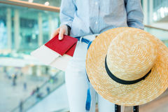 Close-up of passports with boarding pass in female hands. Young woman ready to travel with baggage and straw hat. Closeup of woman holding passports and boarding Royalty Free Stock Photography