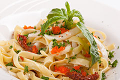 Close up of pasta  with caviar decorated with leaf of basil. Royalty Free Stock Photo