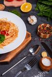Close-up of pasta with grated cheese and meatballs in tomato sauce and basil, on a black background. stock photography