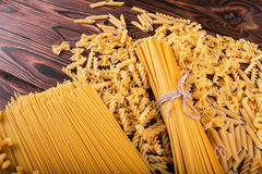 Close-up of pasta on a wooden background. Farfalle, fettuccine, noodles, fusilli and penne rigate. Tasty Italian cuisine Stock Photo