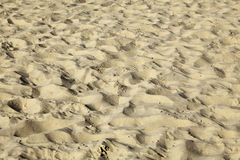 Close up on a patch of beach sand. The sand has been turned over. Countless times by people's feet, leaving it in a total mess Royalty Free Stock Images