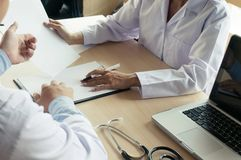 close up of patient and doctor taking notes or Professional medical doctor in white uniform gown coat interview stock image