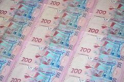 A close-up of a pattern of many Ukrainian currency banknotes with a par value of 200 hryvnia. Background image on business in Ukr. Aine Stock Image