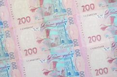 A close-up of a pattern of many Ukrainian currency banknotes with a par value of 200 hryvnia. Background image on business in Ukr. Aine stock photography