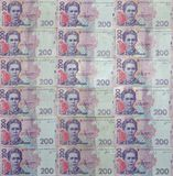 A close-up of a pattern of many Ukrainian currency banknotes with a par value of 200 hryvnia. Background image on business in Ukr. Aine Stock Images