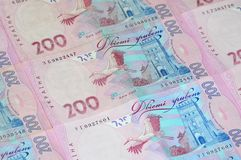 A close-up of a pattern of many Ukrainian currency banknotes with a par value of 200 hryvnia. Background image on business in Ukr royalty free stock image